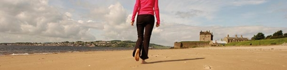 Woman walking along Broughty Ferry beach